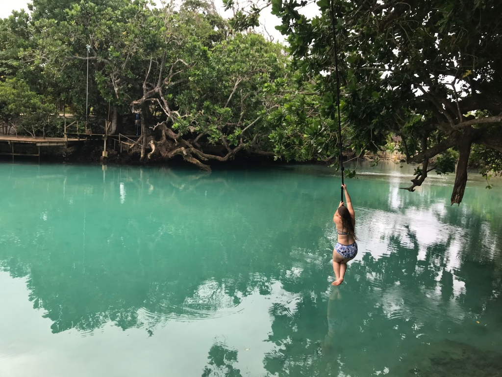 a girl rope swings into an empty lagoon