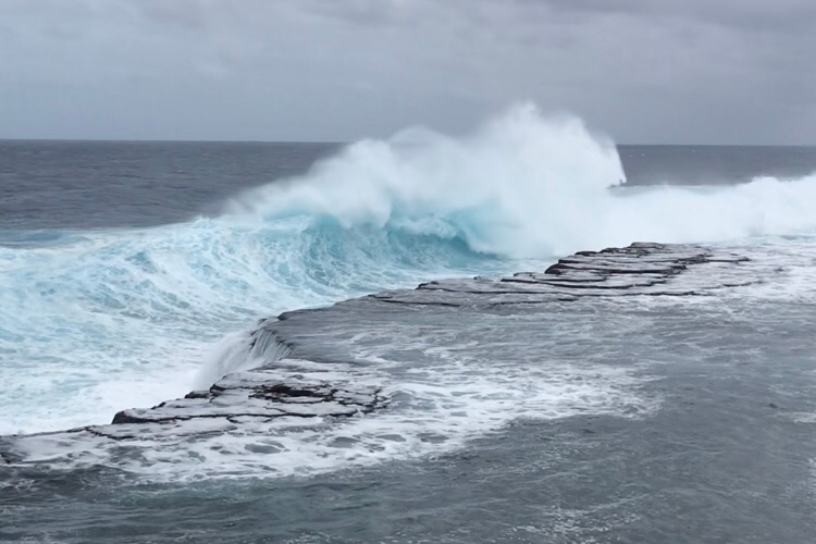 blue waves crashing into the shore below stormy skies