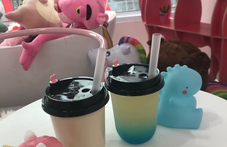 Two colourful cups of milk tea sit on a table between a plastic unicorn and dinosaur.