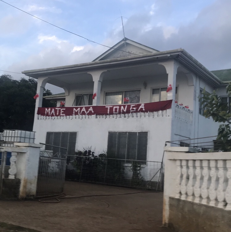 "A sign reads ""Mate Ma'a Tonga"" on a red sign outside a home"
