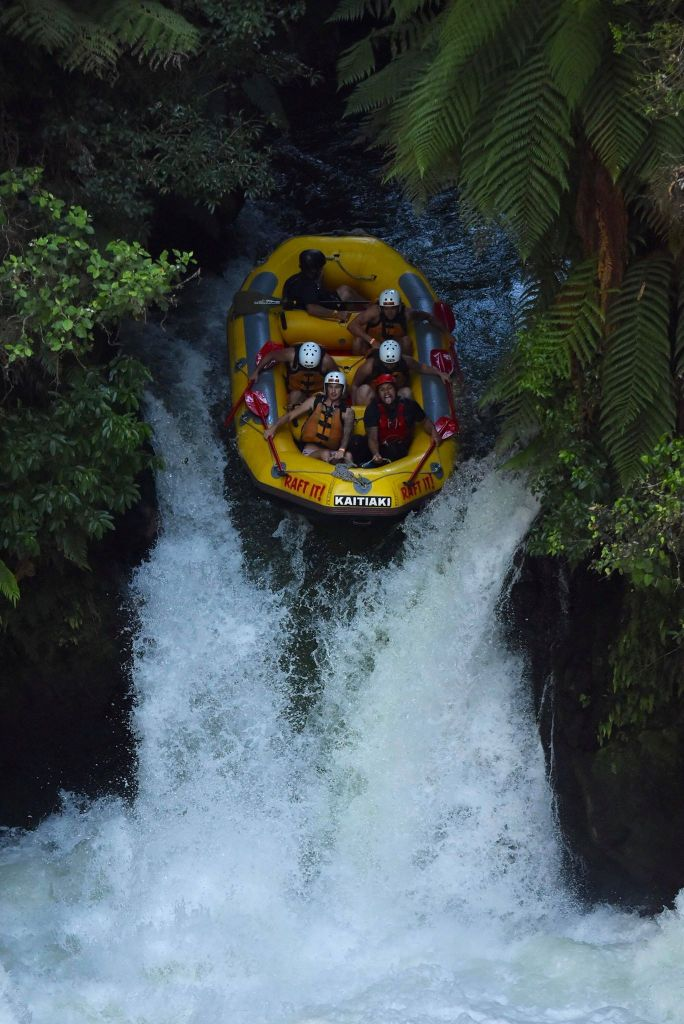 A yellow raft plunging down a large waterfall with 6 people inside, holding on tigh