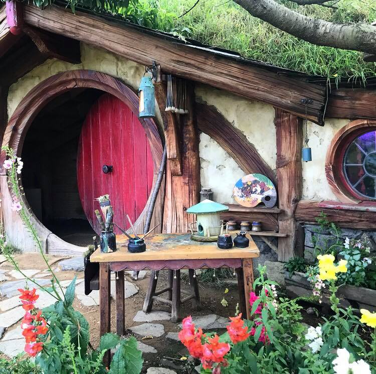 A hobbit hole with a red door slightly adjar, and painting equipment outside for decor