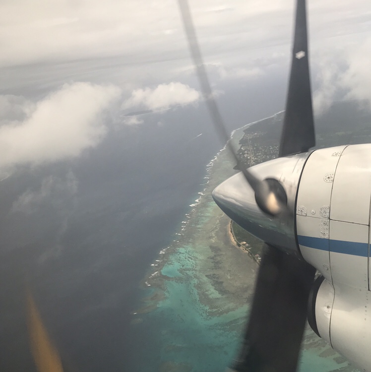 A plane propellor above clouds and turquoise water